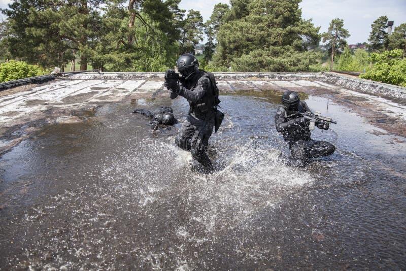 SCHIAFFO degli ufficiali di polizia dei ops di spec. nell'acqua immagini stock libere da diritti