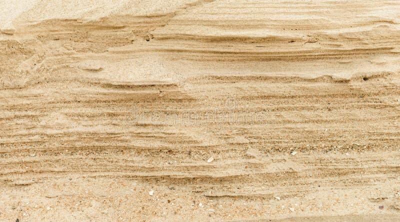 Schichten des Sandes auf dem Strand, weicher Sandstein am Ufer Entziehen Sie Hintergrundbeschaffenheit lizenzfreie stockfotografie