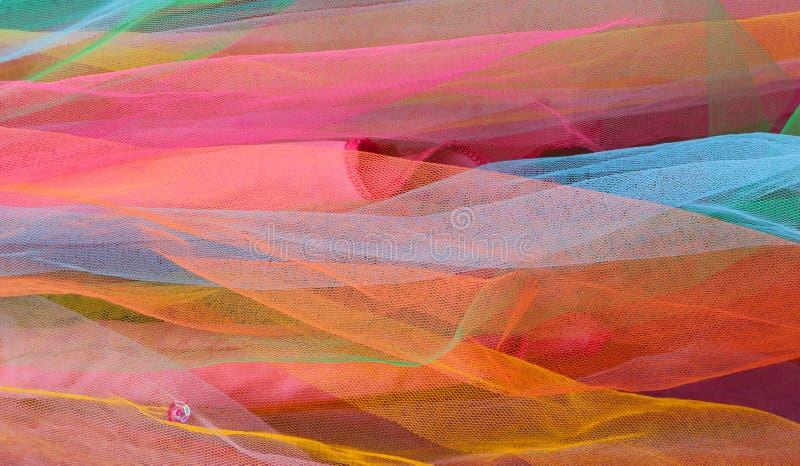 Schichten heller bunter Tulle-Filetarbeit mit rosa Pailletten stockfotos