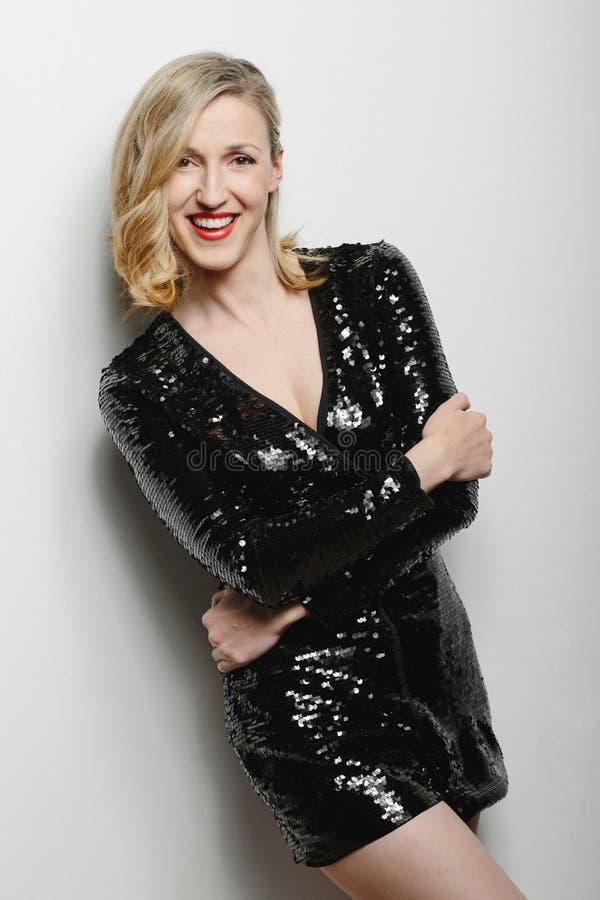 Schicke blonde Frau in einem stilvollen schwarzen Cocktailkleid lizenzfreie stockfotografie