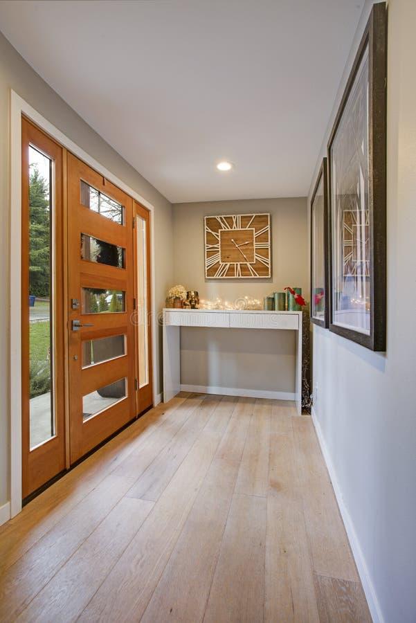 Schickes Foyer mit einer Glasplattenhaustür und weißen einem Tisch für Systemkonsole stockfotografie