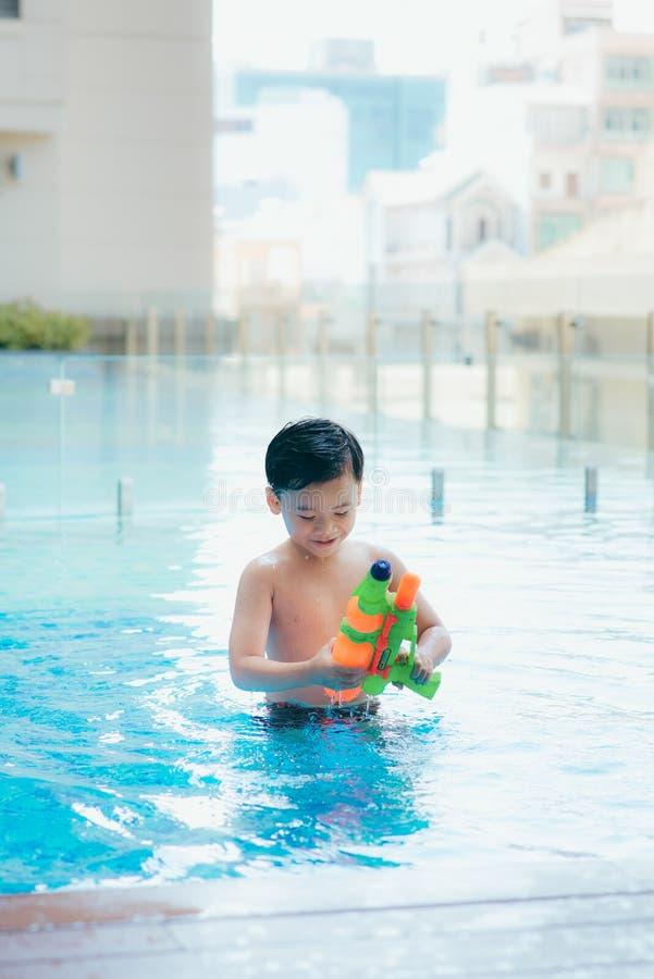 Schießen des kleinen Jungen mit Wasserwerfer im Pool stockfoto