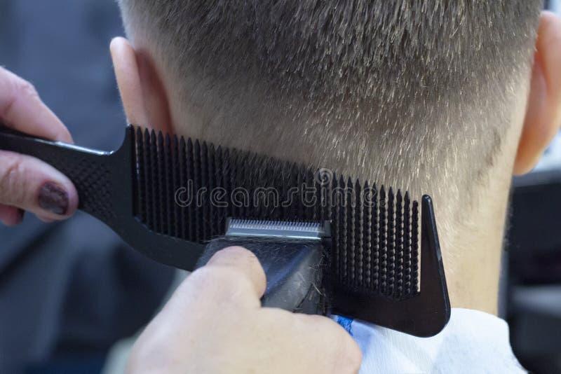Schieben Sie die Heckansicht eines Friseurs mit einem Abklappen, das dem männlichen Kunden einen Haarschnitt verleiht Peitschensc stockbilder