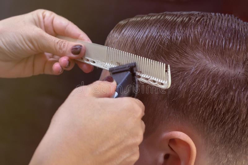 Schieben Sie die Heckansicht eines Friseurs mit einem Abklappen, das dem männlichen Kunden einen Haarschnitt verleiht Peitschensc stockfotografie
