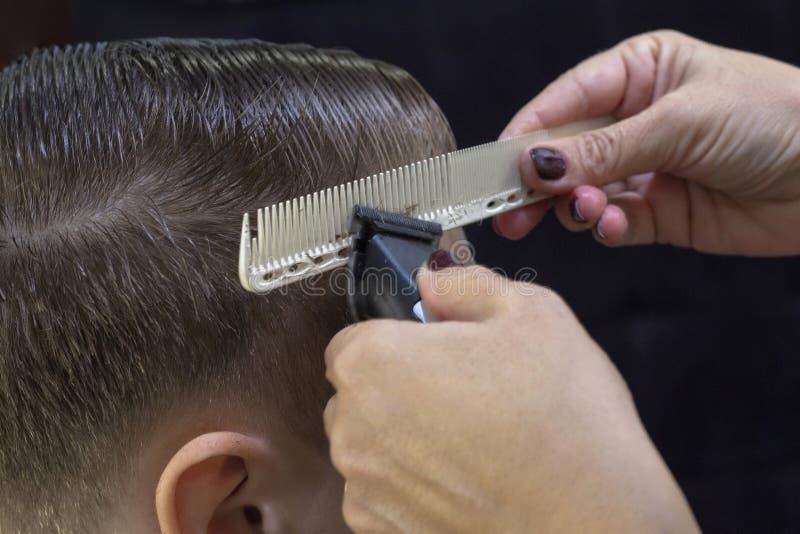 Schieben Sie die Heckansicht eines Friseurs mit einem Abklappen, das dem männlichen Kunden einen Haarschnitt verleiht stockbilder