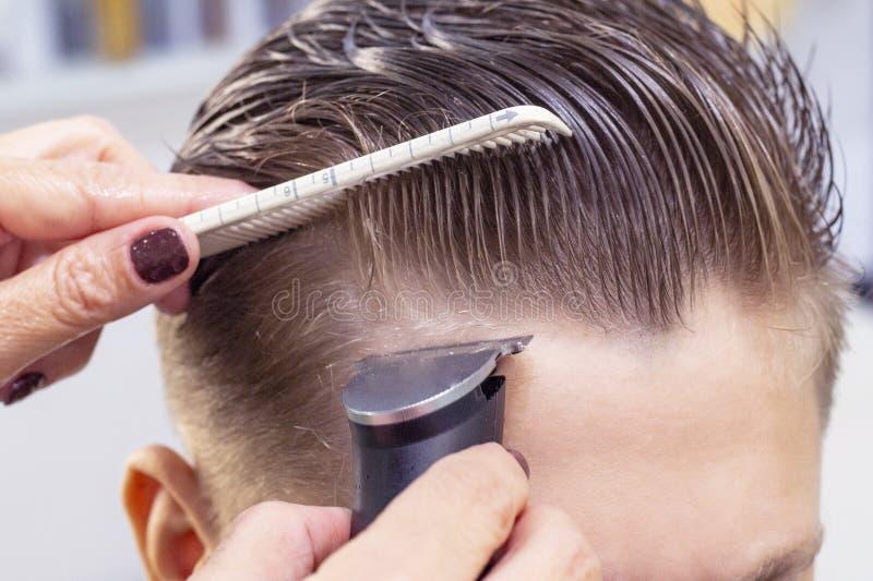 Schieben Sie die Heckansicht eines Friseurs mit einem Abklappen, das dem männlichen Kunden einen Haarschnitt verleiht lizenzfreies stockbild