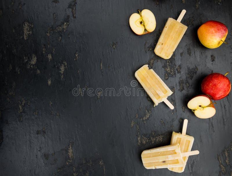 Schieferplatte mit irgendeinem selbst gemachtem Apple-Eis am Stiel stockfoto
