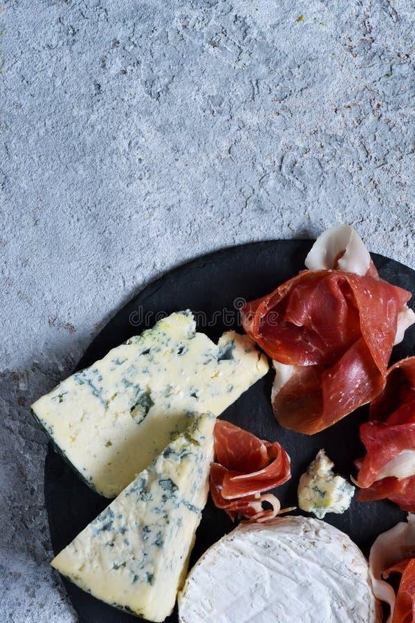 Schieferplatte mit Zartheit: jamon, Blauschimmelkäse, Briekäse stockbilder