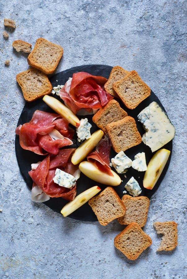 Schieferplatte mit Zartheit: jamon, Blauschimmelkäse, Briekäse lizenzfreie stockfotos