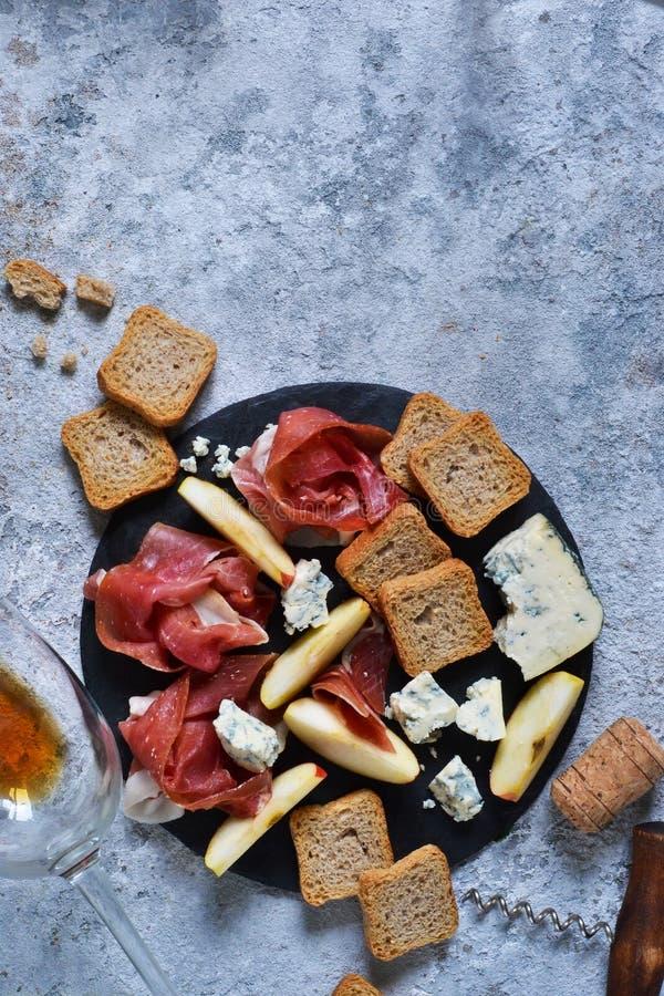 Schieferplatte mit Zartheit: jamon, Blauschimmelkäse, Briekäse und ein Glas rosafarbener Wein lizenzfreie stockbilder