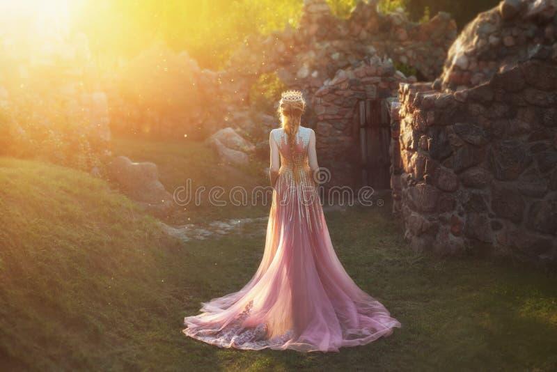 Schietend zonder een gezicht, van de rug Prachtige prinses met blond haar en een kroon draagt lichtrose verbazen stock foto