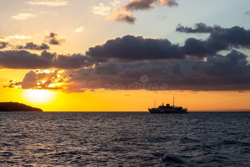 Schiff, das in einen hellen gelben Sonnenuntergang nahe den Istanbul-Inseln segelt lizenzfreies stockfoto