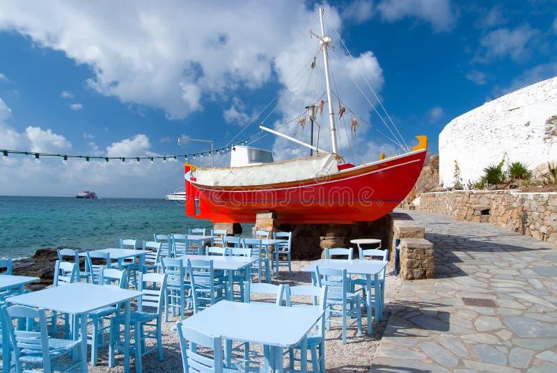 Schiff und Tavernenmöbel auf Kai in Mykonos, Griechenland Rotes Boot und blaue Tabellen auf Meer setzen auf den Strand Strandrest lizenzfreie stockfotografie