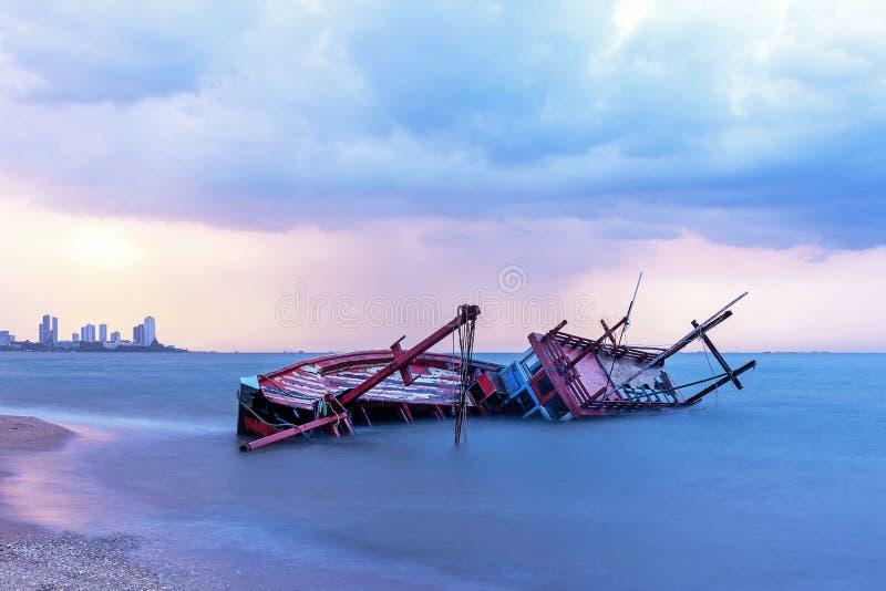 Schiffbruch oder ruiniertes Boot auf Strand im Sonnenuntergang Schöne Landschaft lizenzfreies stockbild
