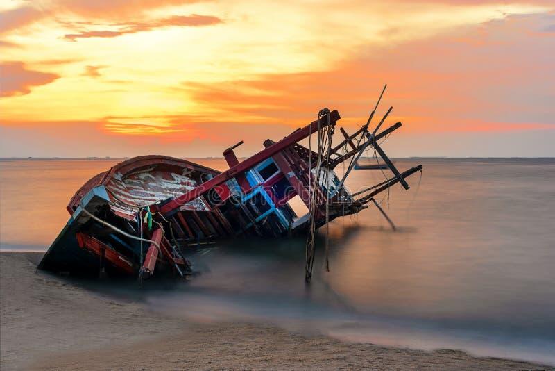 Schiffbruch oder ruiniertes Boot auf Strand im suset Schöne Landschaft stockfotografie