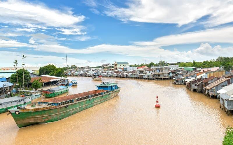 Schiffe kreuzen das Zusammenströmen von Flussuferdörfern stockfoto