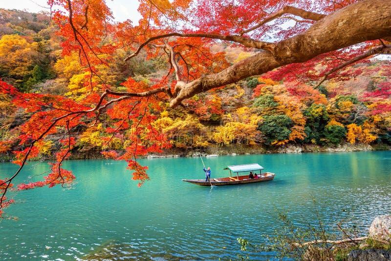Schiffer, der das Boot in Fluss stochert Arashiyama in der Herbstsaison entlang dem Fluss in Kyoto, Japan lizenzfreie stockfotos