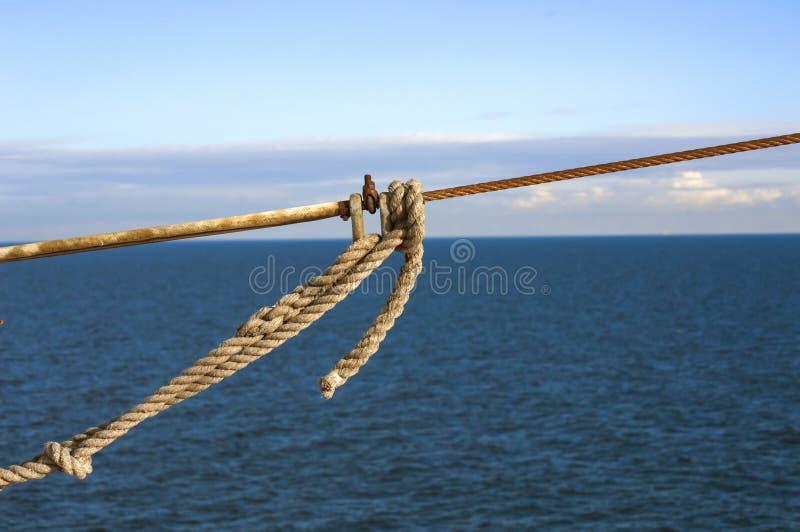 Schiffsseile mit einem Knoten auf blauem Seehintergrund stockfotografie