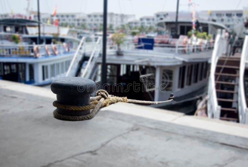 Schiffstau mit geknotet gebunden um einen Bügelen mit Ausflugboot lizenzfreie stockfotos