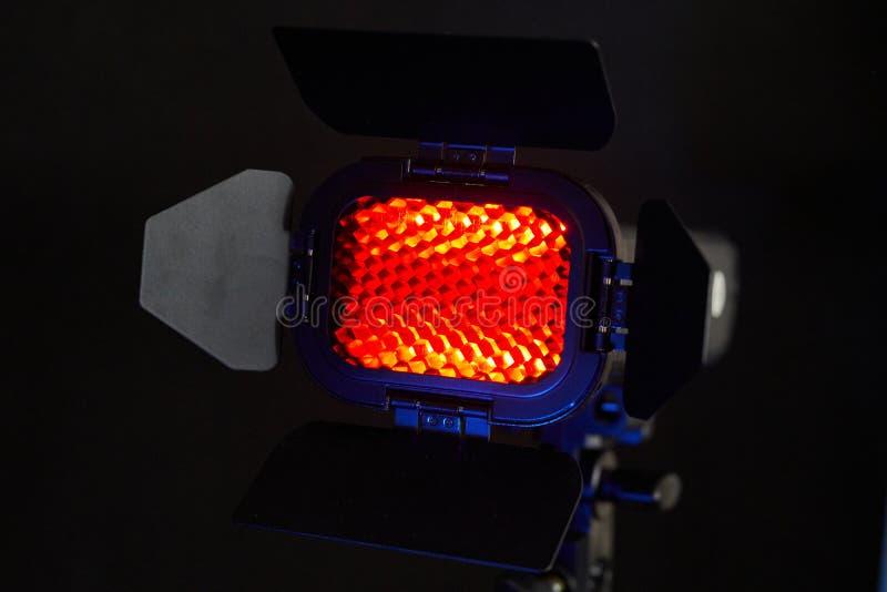 Schijnwerper met rood licht en honingraat Foto en videomateriaal voor de Studio stock fotografie