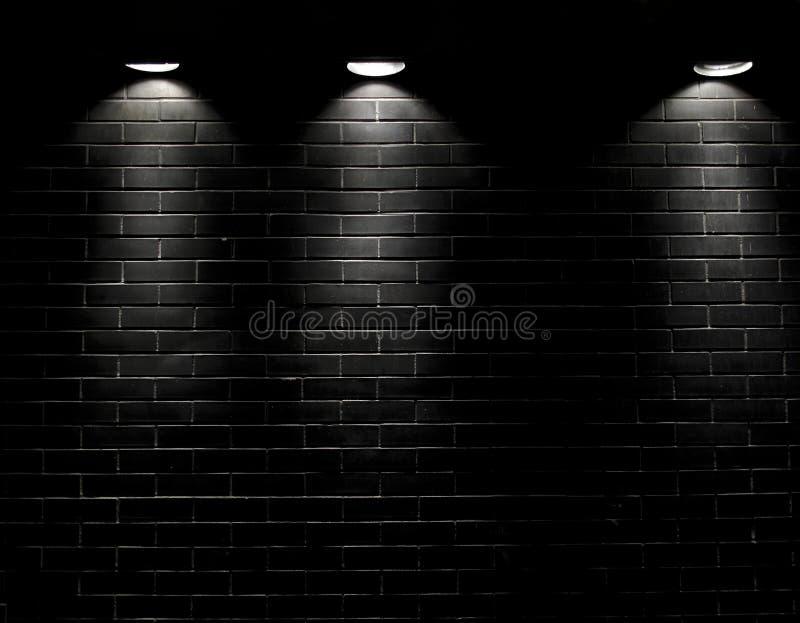 Schijnwerpers op een zwarte bakstenen muur stock afbeeldingen