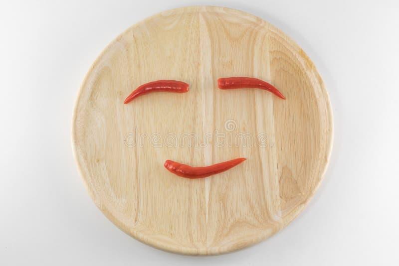 Schik de peper op een houten plaat stock foto's