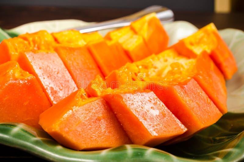 Schik verse gele papaja op groene bladschotel royalty-vrije stock foto