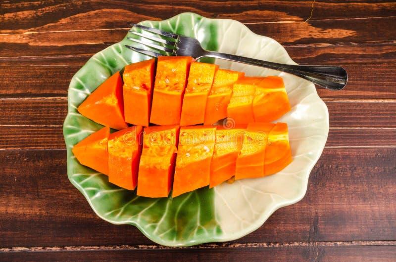 Schik verse gele papaja op groene bladschotel stock fotografie