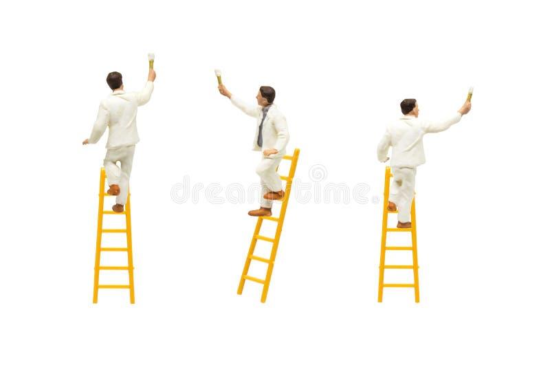 Schilder die zich op houten ladder en het schilderen muur met verfhulpmiddelen bevinden die op witte achtergrond worden ge?soleer royalty-vrije stock foto