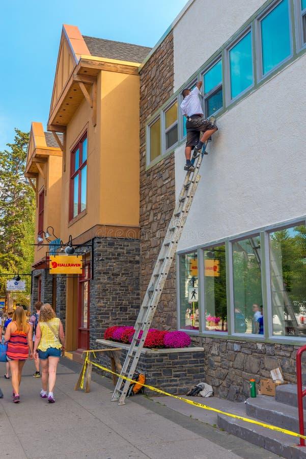 Schilder het schilderen vensterversiering in Banff-Bedrijfsdistrict stock foto
