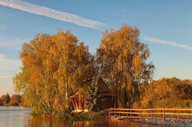 Schilderachtig landschap van klein eiland met verlaten huis en bomen in het midden van het meer Het landschap van de de herfstoch royalty-vrije stock fotografie