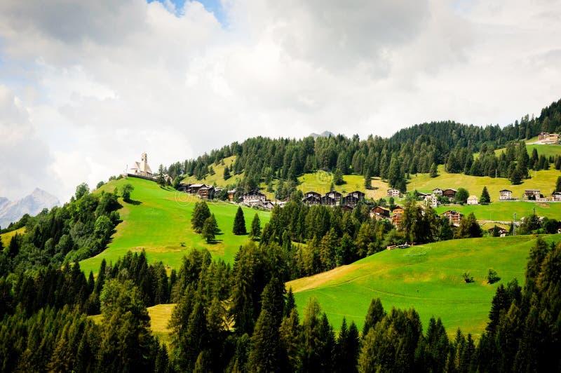 Schilderachtig Oostenrijks dorp met kerk vóór onweer De Alpen op achtergrond royalty-vrije stock afbeelding