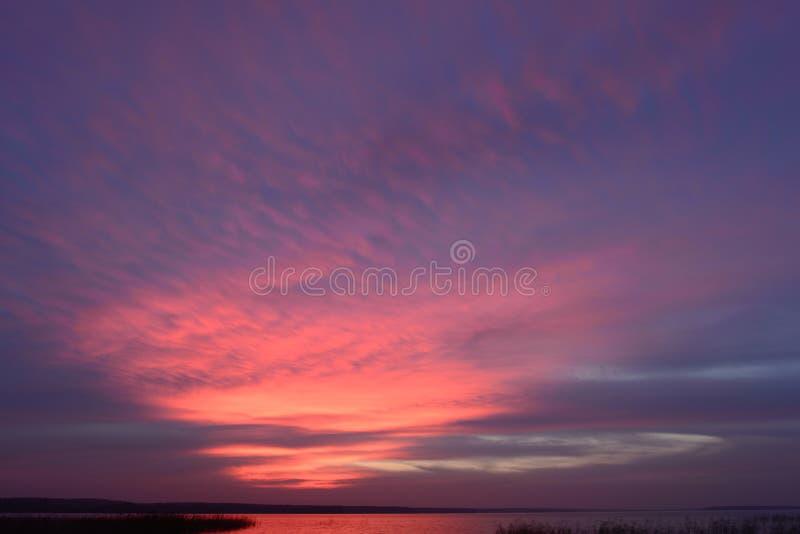 Schilderachtige de herfst de schemeringhemel in de heldere het gloeien kleuren van de zonsondergang boven de waterspiegel van het royalty-vrije stock foto
