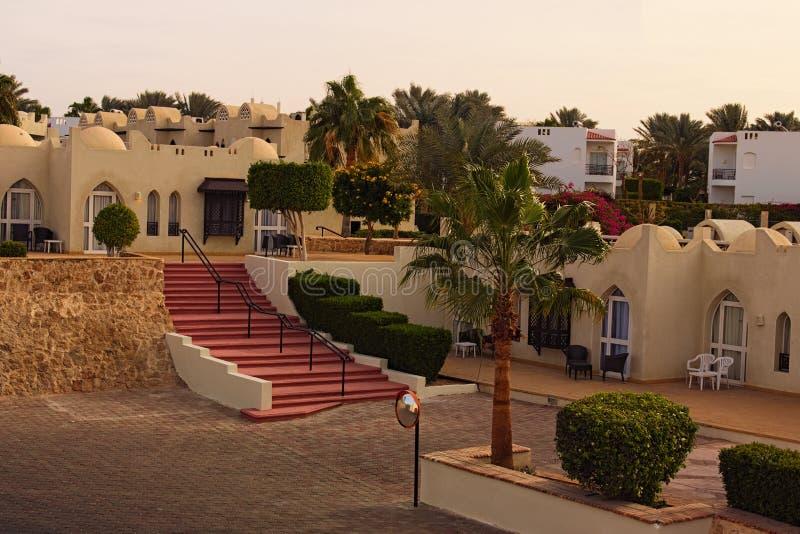 Schilderachtige ochtendmening van hotel de bouw van toevlucht met palmen en struiken tijdens zonsopgang Grsjeik van Sharm, Egypte stock fotografie