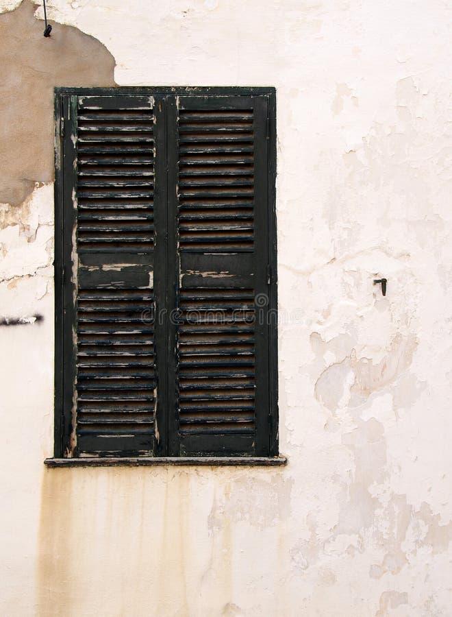 Schilderachtige oude dichte houten geschilderd blinden donkergroen op de vergoelijkte afschilferende schil verontruste oude huism stock fotografie