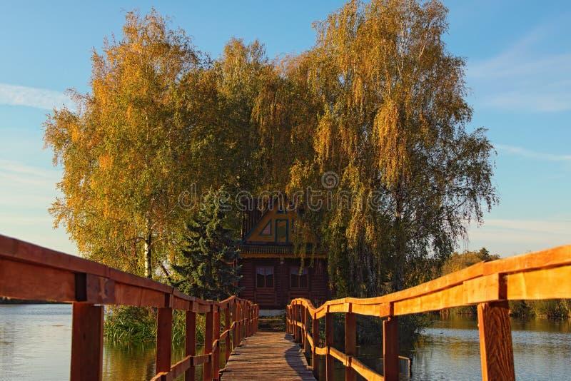Schilderachtige plaats met verlaten huis en bomen in het midden van het meer Het landschap van de de herfstochtend Dorp van Oude  royalty-vrije stock foto's