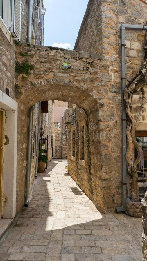 Schilderachtige smalle straat in oude stad van Budva, Montenegro Oude huizen Steenboog binnen de vesting royalty-vrije stock foto