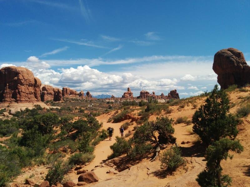 Schilderachtige woestijnscène met rotsvormingen, struiken, en wolken stock afbeeldingen