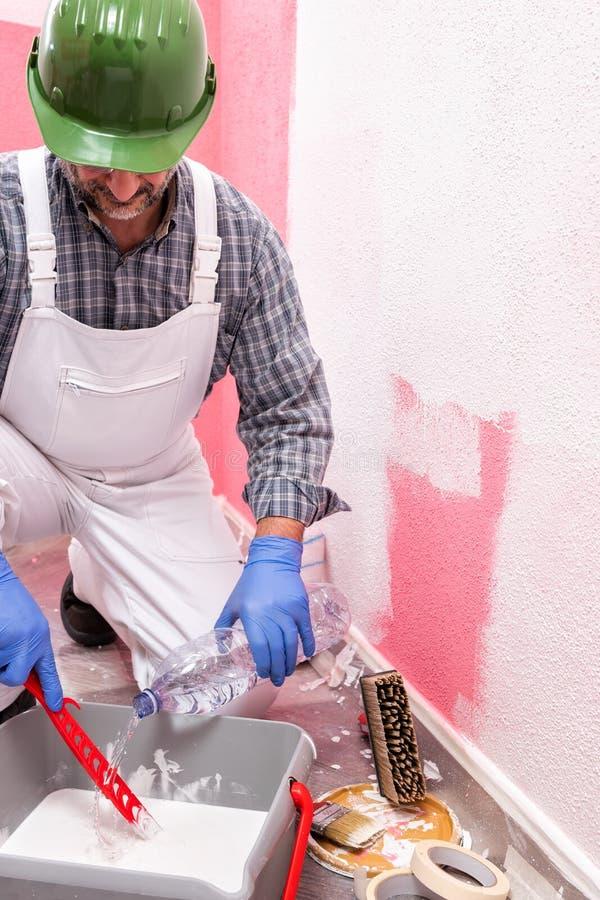 Schilderarbeider aan het werk in de bouwwerf De bouw royalty-vrije stock foto