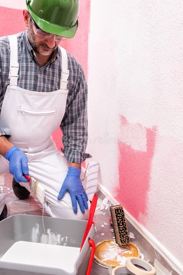 Schilderarbeider aan het werk in de bouwwerf De bouw royalty-vrije stock fotografie