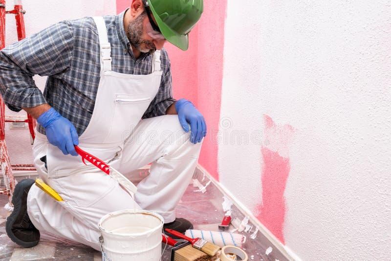 Schilderarbeider aan het werk in de bouwwerf De bouw stock foto