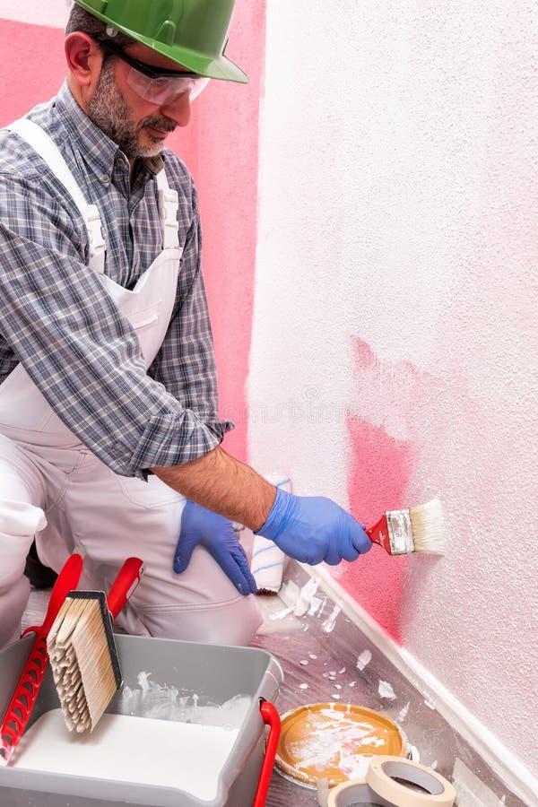 Schilderarbeider aan het werk in de bouwwerf De bouw stock afbeeldingen