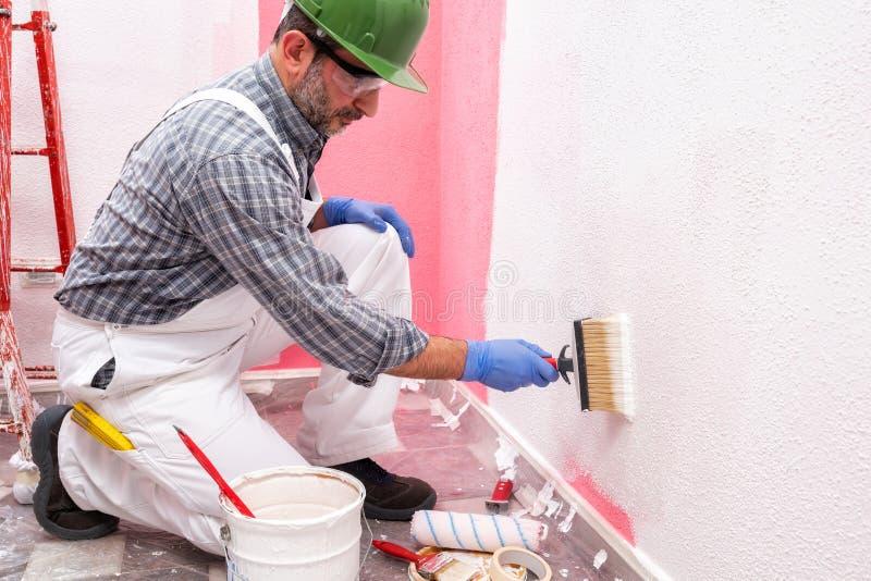 Schilderarbeider aan het werk in de bouwwerf De bouw stock fotografie