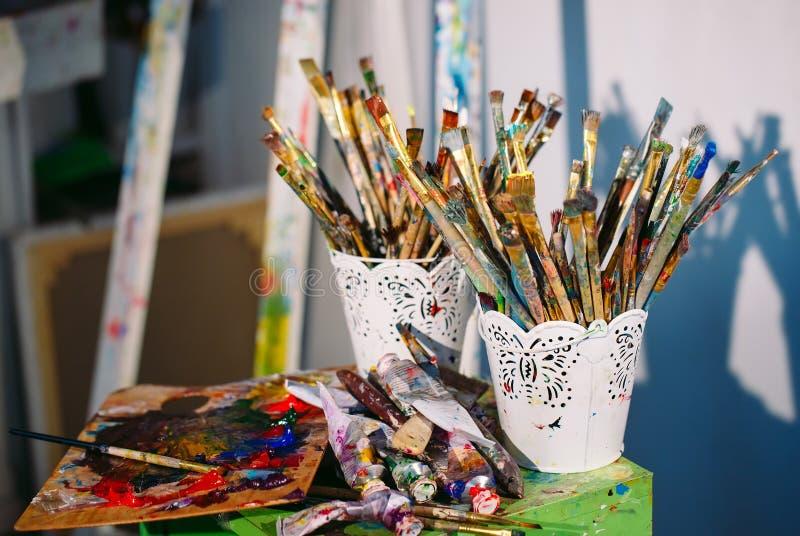 Schilderende Studio EEN vuile borstels in een emmer stock afbeelding