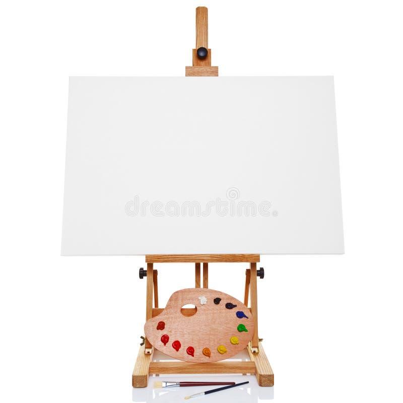 Schildersezel met de de lege verf en borstels van het canvaspalet stock afbeeldingen