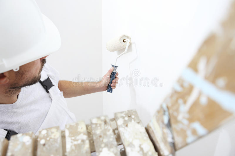 Schildersmens aan het werk met verfrol, op ladder, muurpaintin stock foto