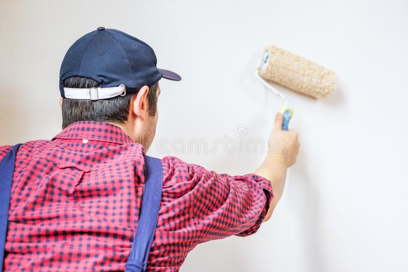 Schildersmens die de muur met verf schilderen royalty-vrije stock afbeelding