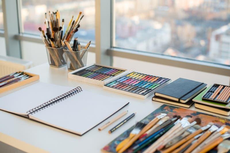 Schilderswerkplaats in orde zijaanzicht Ontwerperbureau met tekeningsmateriaal Huisstudio voor kunstenaar stock foto's