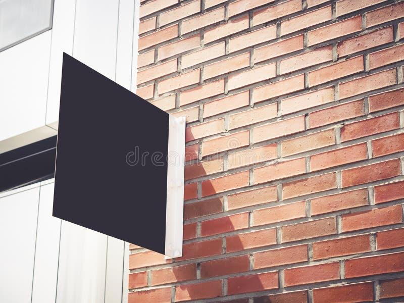 Schildshop Spott herauf schwarze Metallschildanzeige auf Backsteinmauer lizenzfreie stockfotos