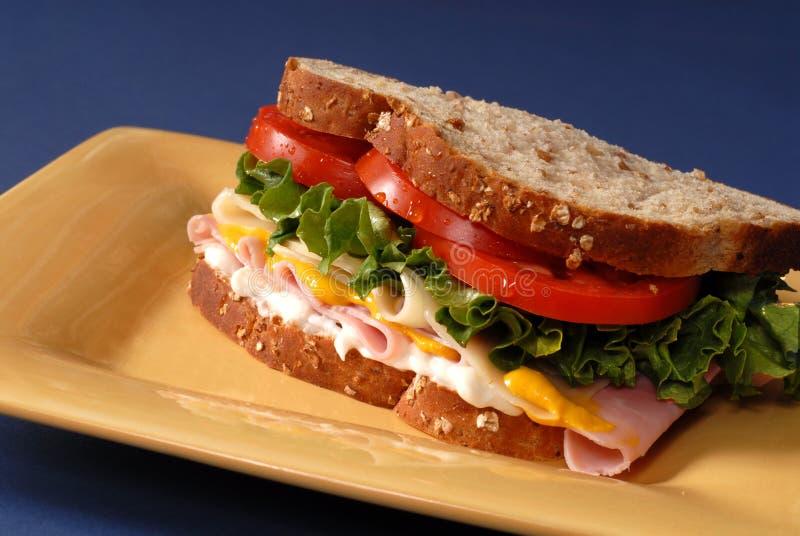 Schinken-, Käse-, Kopfsalat- und Tomatesandwich auf gelber Platte lizenzfreie stockfotografie